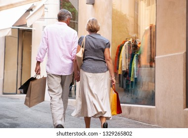 Rear view of tourist senior couple holding hands walking in luxury shopping street carrying bags, vacation trip, outdoors. Mature consumer people on city break travel, leisure recreation lifestyle.