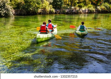 Rear view of tourists paddling kayaks down the green river Sorgue in Fontaine- de-Vaucluse. Kayaking, canoeing, paddling. Provence, France.