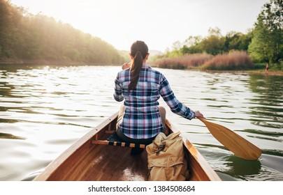 Rear view of travel girl paddling wooden canoe on the sunset lake
