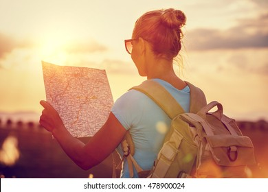Rear view of a traveler girl with backpack exploring map, enjoying mild sunset light, active people lifestyle, summer fun vacation, traveling around the world
