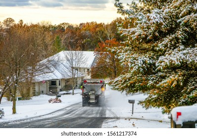 Rear view of truck with snowplow plowing suburban Midwestern street after first snowfall; some trees preserve their colorful fall leaves; Missouri