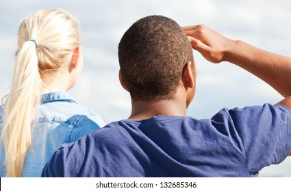 Rear view of two attractive young person staring into the distance.