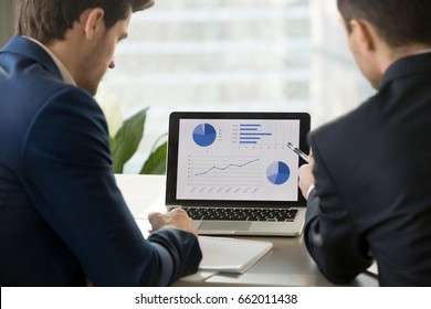 Rear view at two businessmen analyzing stats financial data on pc laptop, pointing at screen with rising graph and charts, discussing company growth, using easy accounting software for small business