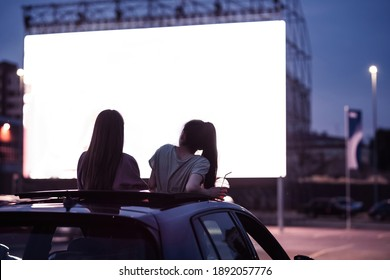 Rear view of two female friends sitting in the car while watching a movie in an open air cinema with a big white screen. Entertainment concept. Focus on people. Horizontal shot - Shutterstock ID 1892057776