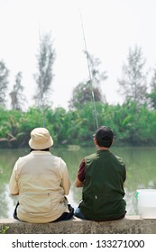 Rear view of two fishers waiting for fish
