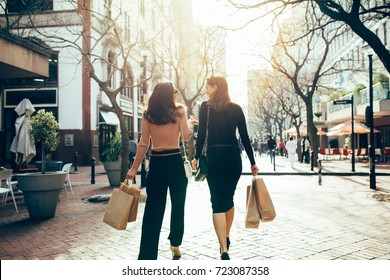 Rear view of two friends walking on the city street with shopping bags. Female shoppers carrying shopping bags while walking along the road.