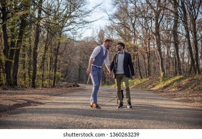 rear view, two gay man walking in forest, on asphalt road. Together holding hands, smiling talking and free. Looking at each other, face to face.