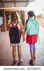 Rear view of two girls going to school and holding hands