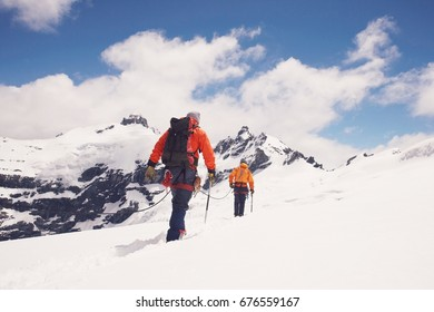 Rear view of two hikers joined by safety line in snowy mountains