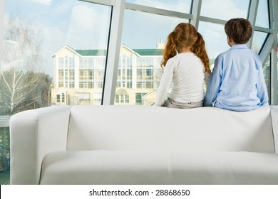 Rear view of two kids sitting on white sofa and looking through window