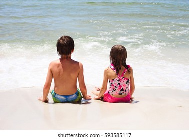 Rear view of two little children sitting together on sand and looking at sea waves. Siblings or friends resting together on beach during summer vacation