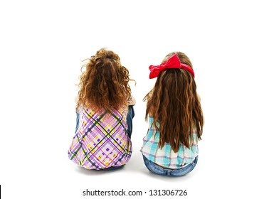 Rear view of two little girl sitting on floor and looking up. Isolated on white background