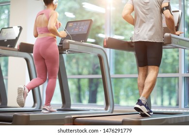 Rear view of two people running on treadmills in gym during cardio workout, copy space