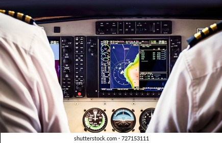 Rear view of two pilots driving a plane with board console and all flight commands. Pilot and copilot flying on small aircraft above tropical island and looking on cockpit. Captain in control cabin.