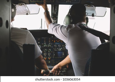 Rear view of two professional pilots dressed in white uniform sitting in private cabin of the plane to control cockpit engine of airplane in air. Flight desk control panel during take off or landing