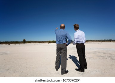 Rear view of two property developers talking plans.