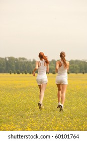 rear view of two woman running in a park