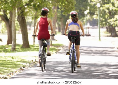 Rear View Of Two Women Cycling Through Park