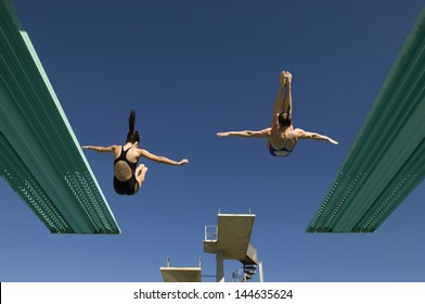 Rear view of two women diving from diving boards against clear blue sky