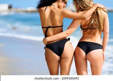 Rear view of two young women with beautiful bodies in bikini having fun on a tropical beach.