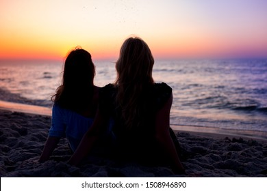 Rear View Of Two Young Women Looking At Sea At Sunset. Silhouettes of two young women watching at beach at colorful sunset