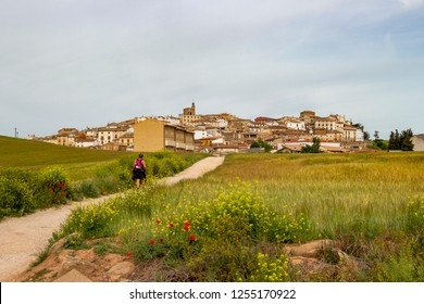 Rear view of an unidentified female pilgrim walking on the Way of St. James, Camino de Santiago towards Cirauqui in Spain, the Cirauqui or Zirauki urban skyline in the distance