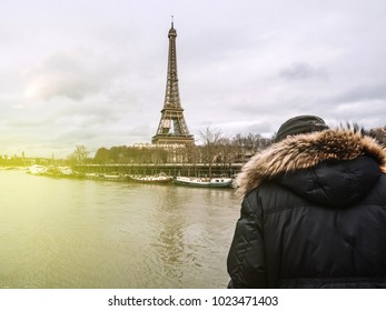 Rear view of Unrecognizable Parisian senior man watch the swollen river Seine near the Eiffel Tower as the river's embankments overflow after days of heavy rain sunflare