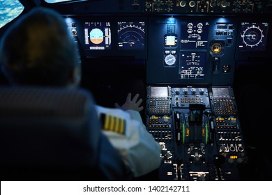 Rear view of unrecognizable pilot sitting at control panel with radar devices and flight system buttons and flying plane on autopilot