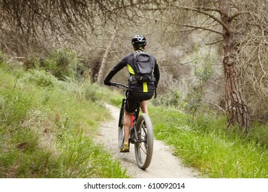 Rear view of unrecognizable rider cycling on his booster bicycle on trail outdoors, enjoying fresh air in forest. Male biker riding motor-powered electric bike during morning workout in countryside