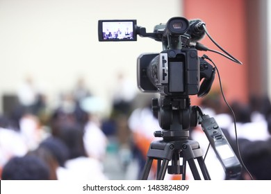 The rear view of the video recorder is recording the live event with blurred audience and lecturer background, show, dept, technology concept.