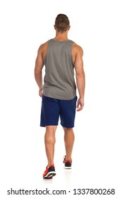 Rear view of walking fit man in gray tank top, blue shorts and orange sneakers. Full length studio shot isolated on white.