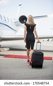 Rear view of wealthy woman with luggage walking towards private jet at airport terminal