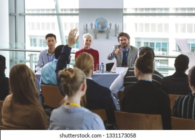 Rear view of well dressed businessman raising hand while Caucasian colleague allows him to speak at a business seminar in office building