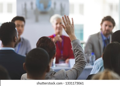 Rear view of well dressed businesswoman raising hand while Caucasian woman allowed her to speak at a business seminar in office building
