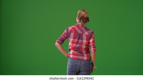 Rear view of white female gardener with gloves standing on green screen