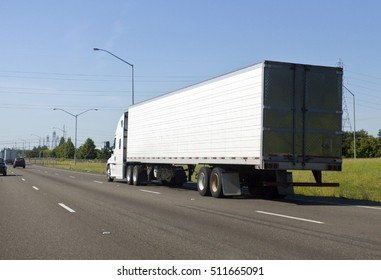 Rear view of white semi on highway under blue sky.