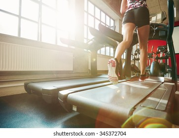 Rear view of woman in action running on treadmill. Focus on woman legs exercising on treadmill at the gym.