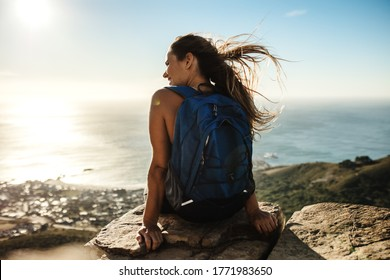 Rear view of a woman with backpack sitting on the cliff and looking at the view Female hiker relaxing on mountain top.