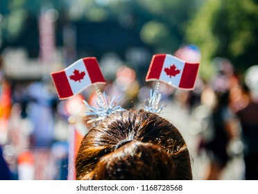 Rear view of woman with Canada flag antennas on head walking on street in Windsor for royal wedding marriage celebration of Prince Harry, Duke of Sussex and the Duchess of Sussex Meghan Markle