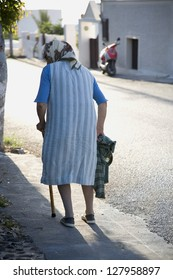 Rear view of woman with cane and head scarf walking down street