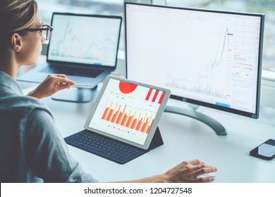 Rear view of woman financial specialist studying theory and practice blockchain technology. Female broker sitting front computer with graphs statistics of stock exchange. Earnings on raising quotes