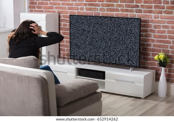 Vista Trasera De Una Mujer Frustrándose Con Una Pantalla De Televisión Con Glitch En Casa