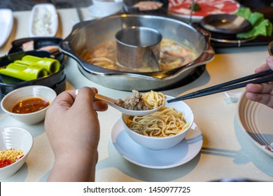 Rear view of woman hands eating hotpot