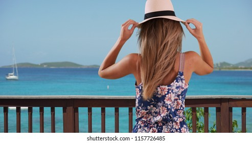 Rear view of woman in her 20s holding her hat on oceanfront patio