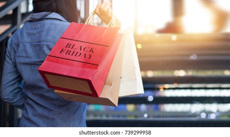 Rear view of woman holding Black Friday shopping bag while up stairs outdoors on the mall background