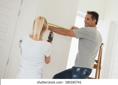 Rear view of a woman holding drill while man measuring the wall at new home