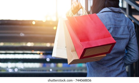 Rear view of woman holding shopping bag while up stairs outdoors on the mall background