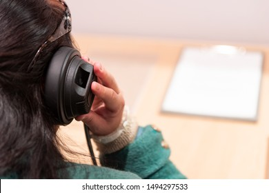 Rear view of woman listening to headphones with desk and white paper in front