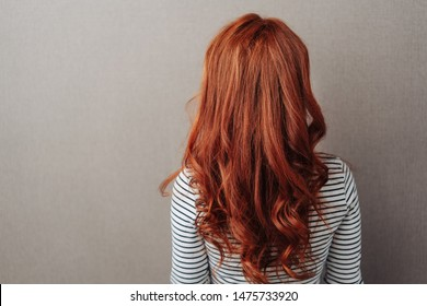 Rear view of a woman with long curly red hair standing facing a grey wall with copy space