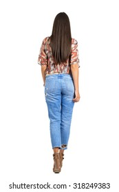 Rear view of woman with long hair in casual clothes walking away. Full body length portrait isolated over white studio background.